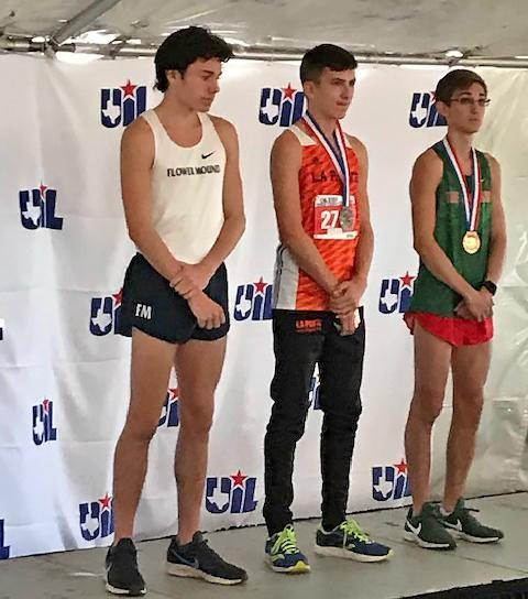 Three high school students standing on winner's podium