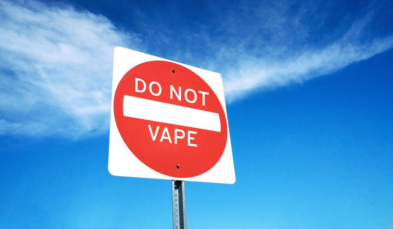 A stop sign with the words 'Don't Vape' against the backdrop of a partly-cloudy sky