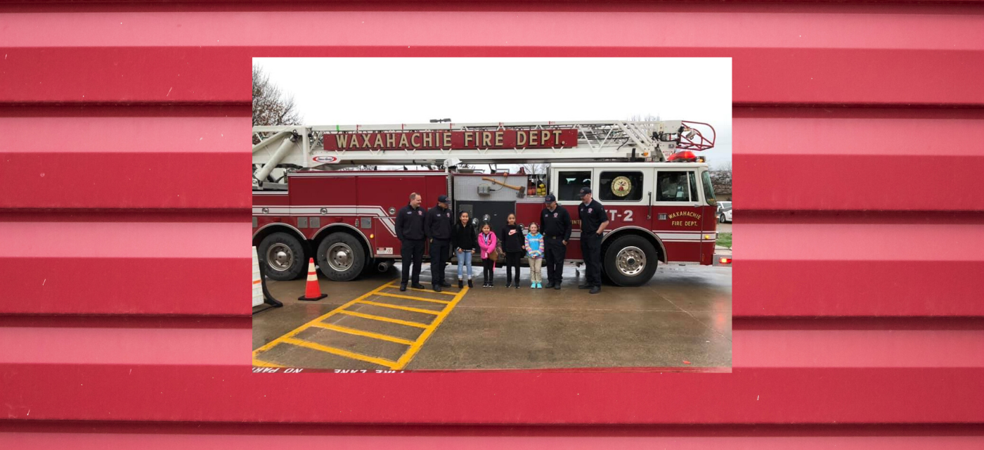 four students pose with four firemen in front of firetruck