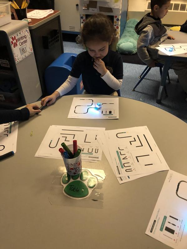 close up of girl testing her coding on the sheet of paper