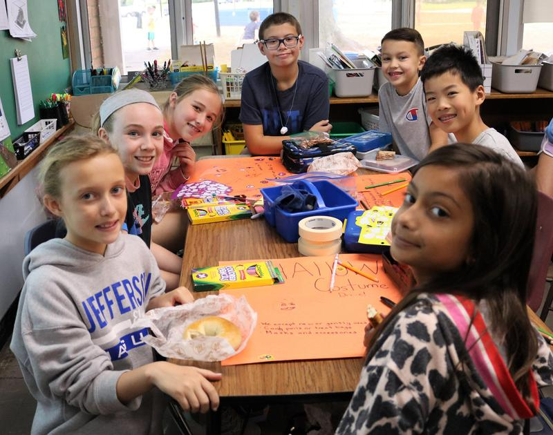 Photo of student members of Jefferson School Early Act Club creating posters for Halloween Costume Drive.
