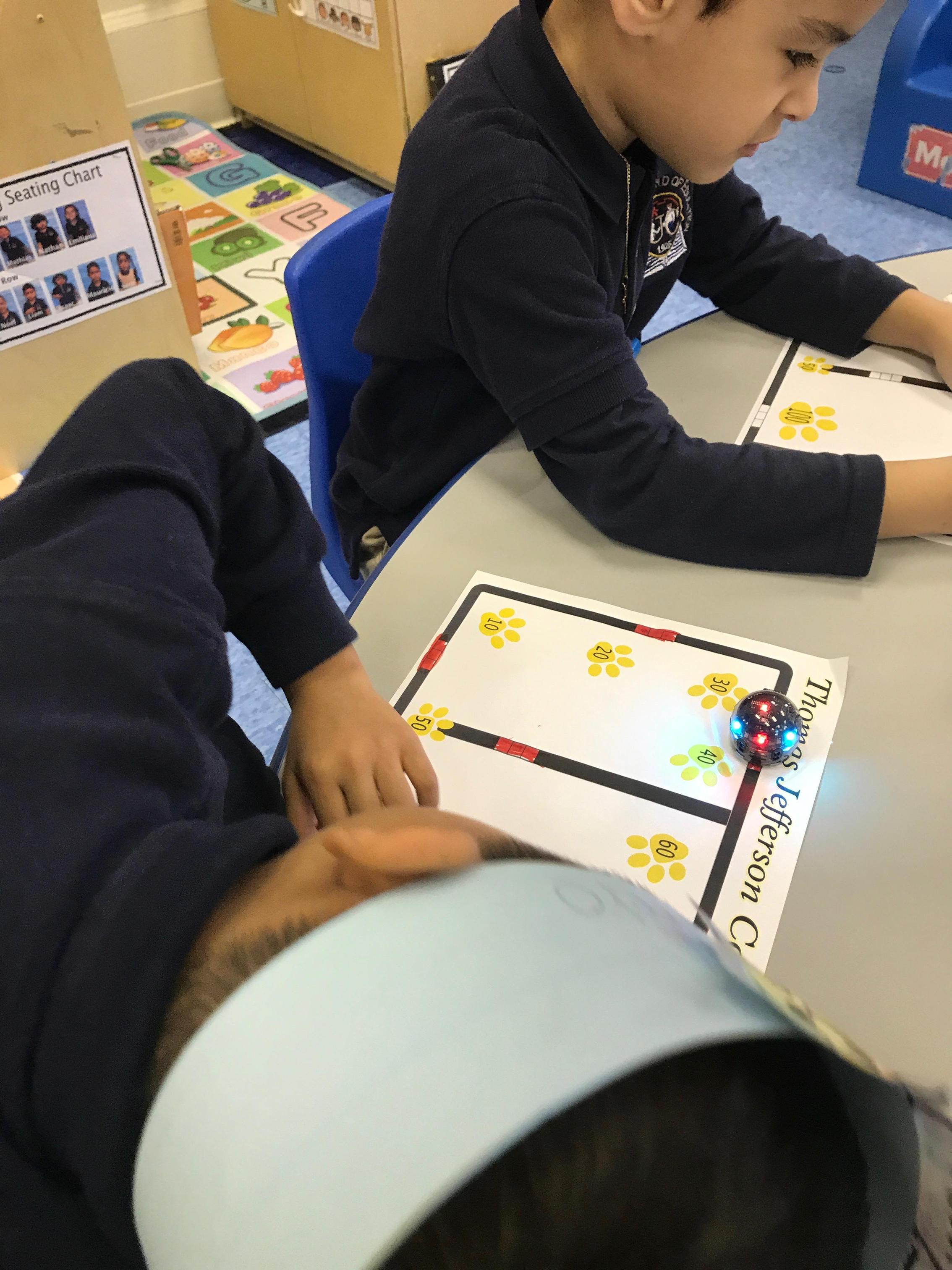 student at the table working with Ozobot