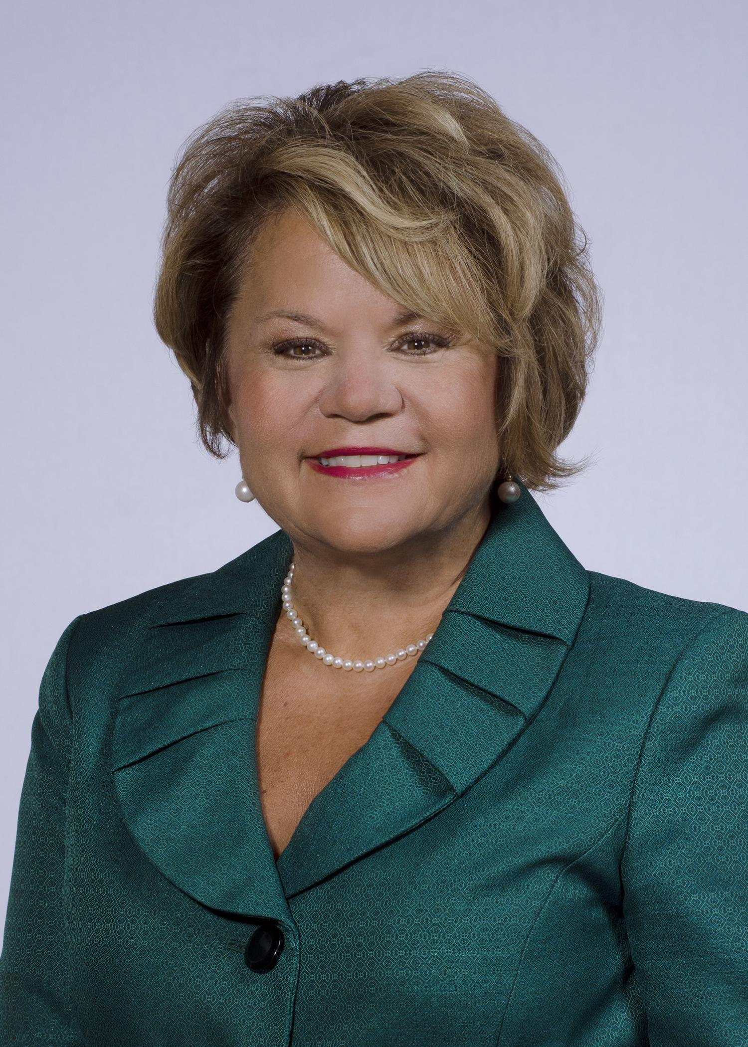 The image is a headshot of Dr. Melody Hackney, Superintendent for Hopewell City Public Schools. Her hair is blonde, she is smiling, and is wearing a green jacket with a scalloped collar.