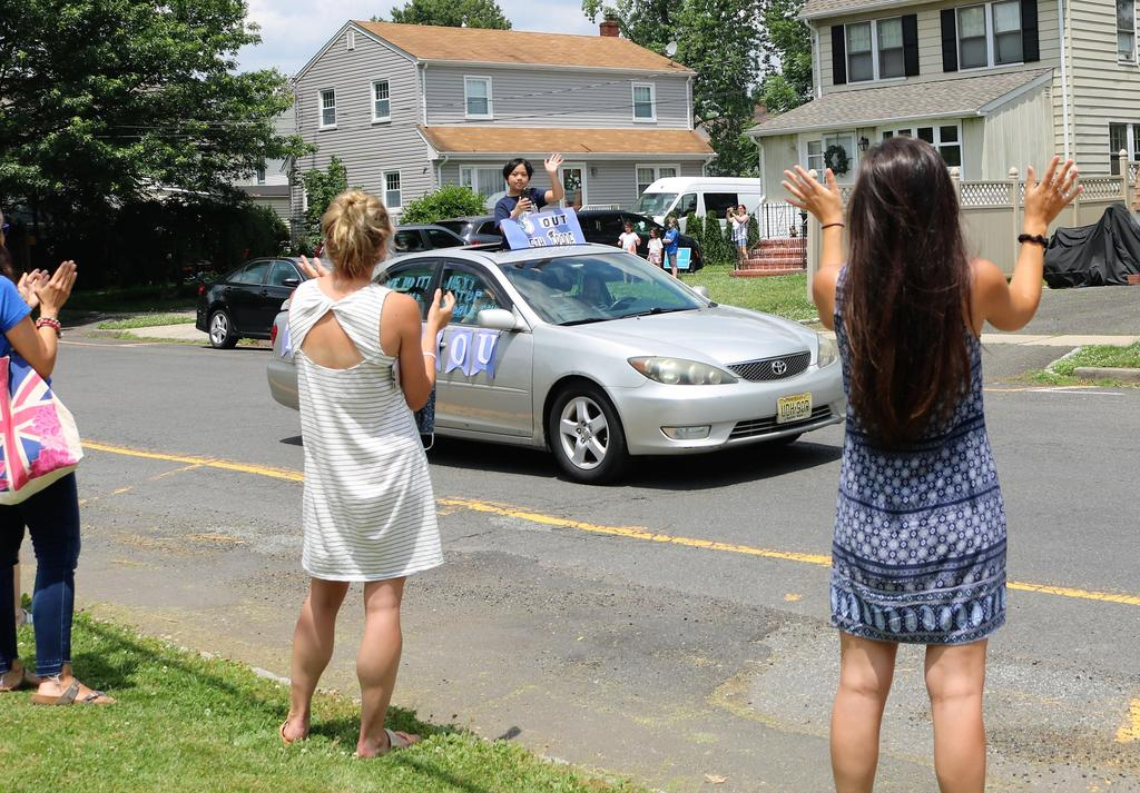 Photo of McKinley staff waving to 5th graders passing by during Grade 5 Clap Out Car Parade
