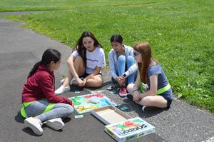 4 girls sitting on the ground playing the board game