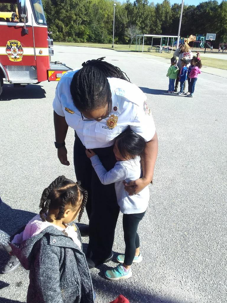 Fire and Life Safety Educator hugs student with the fire truck in the background.