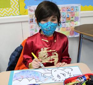 Photo of Franklin 2nd grader using watercolors to paint the legendary Chinese Dragon, during China Day activities
