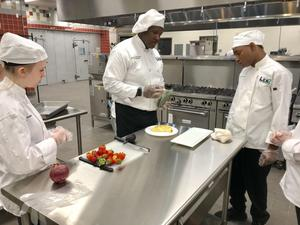 Instructor and Chef Isaac Pressley, center, teaches Lexington Two culinary arts students the finer points of making omelets.
