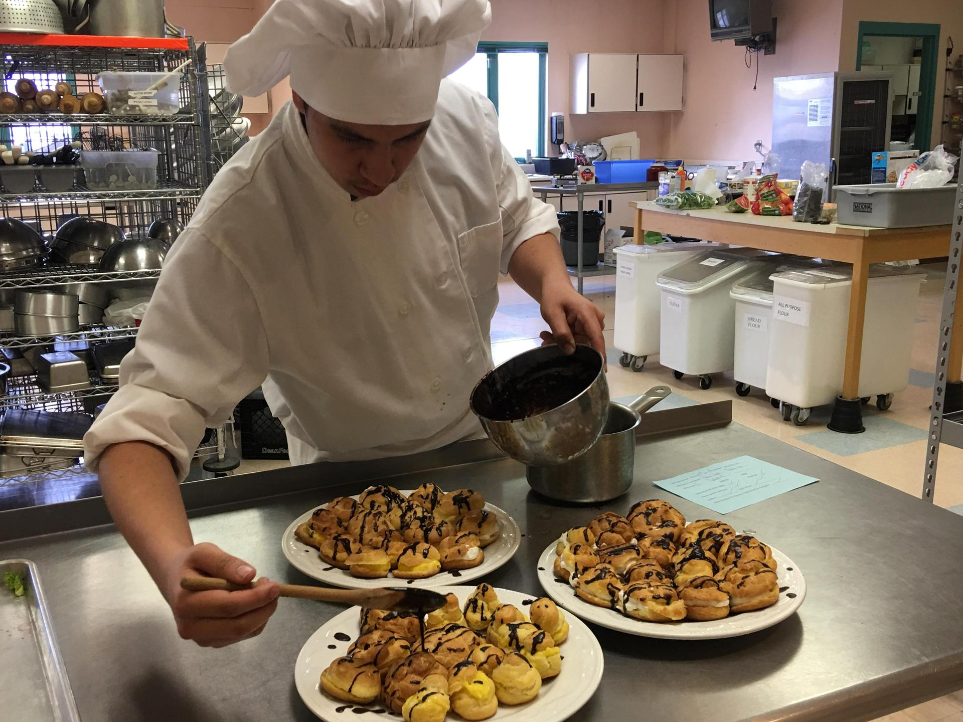 Culinary Art Student from Gallup High adding the finishing touch to his cream puffs