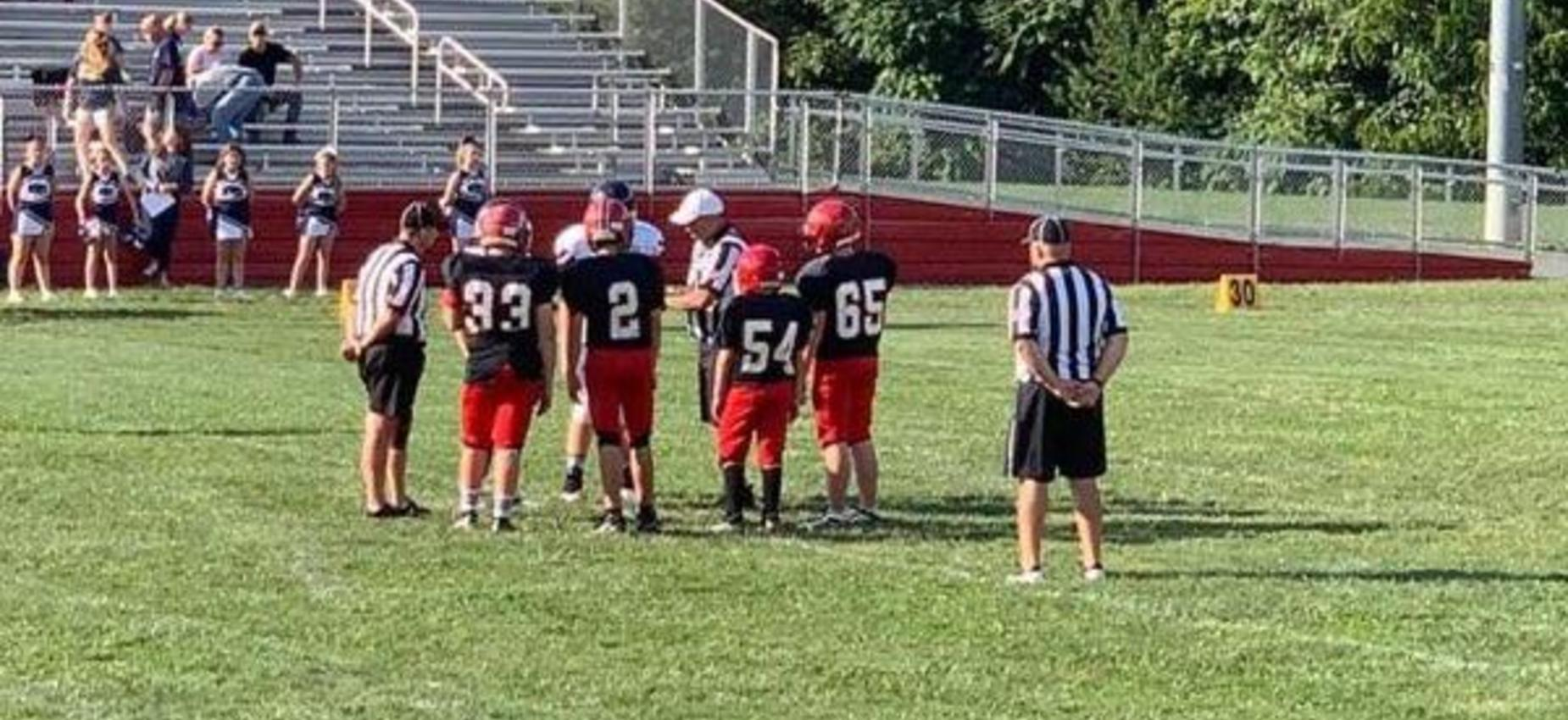 Football players meet with referees for a coin toss on a field.