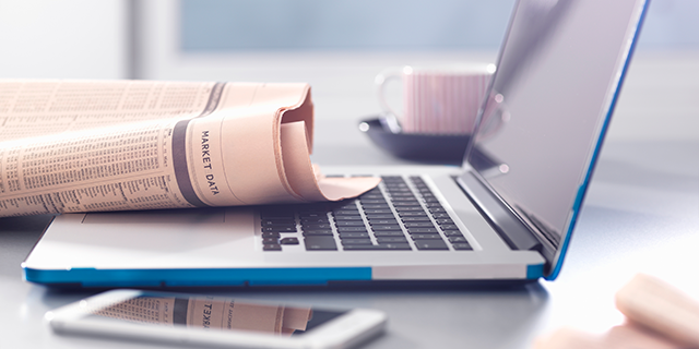 newspaper sitting on laptop