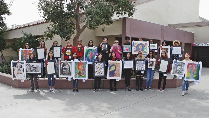 Students holding award winning art work