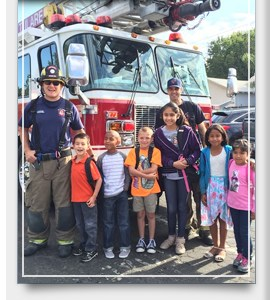 Children and Firefighters standing in front of fire truck
