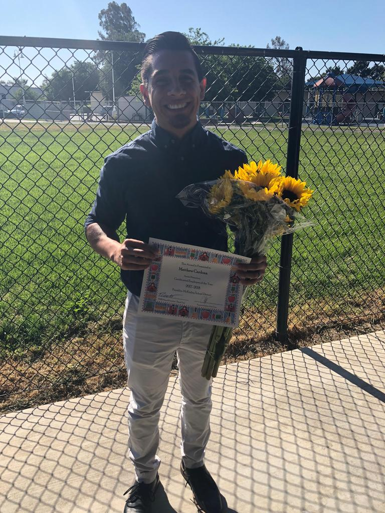 matthew cardona, certificated staff of the year, poses with flowers and certificate