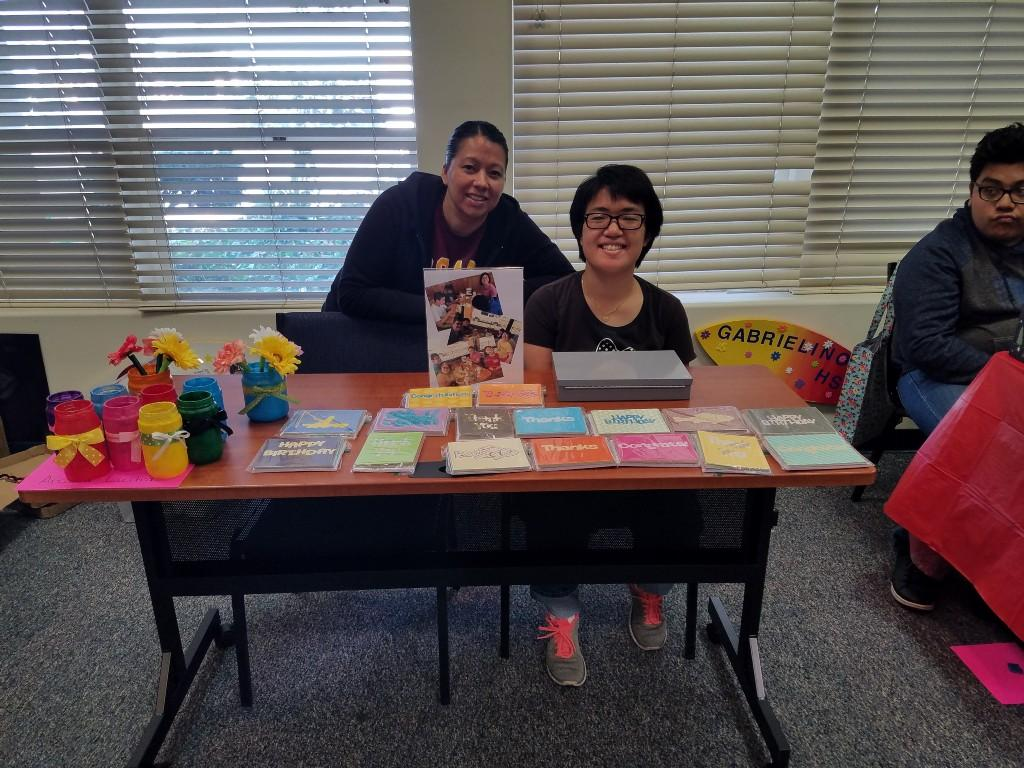 Student and teacher sitting at table selling crafts