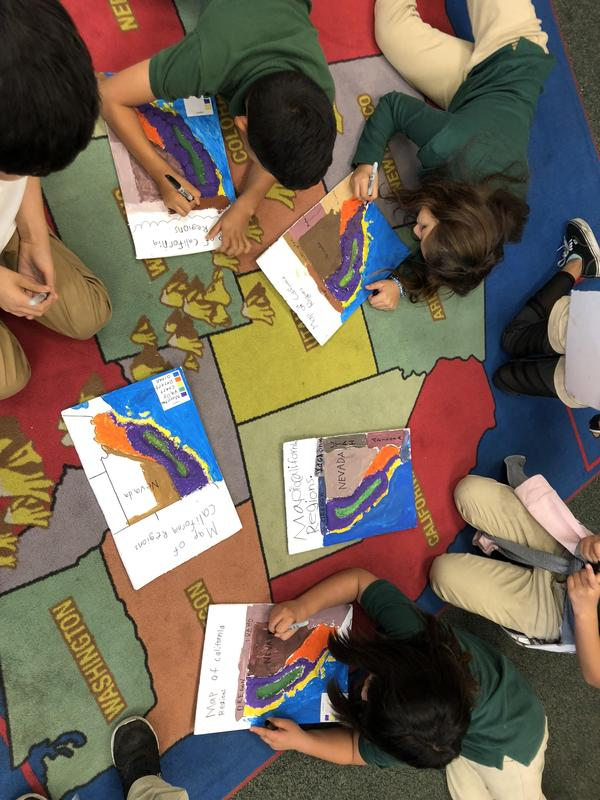 Students use the classroom carpet to help label their maps