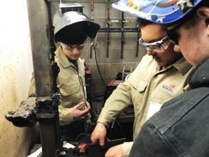 3 boys working on large piece of metal