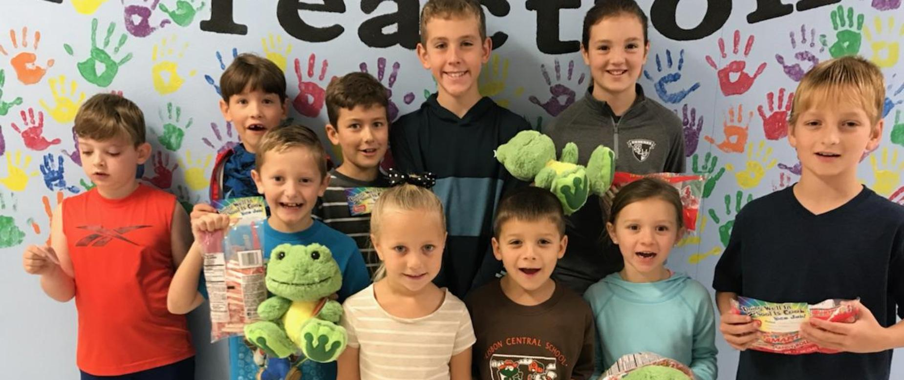 group of about ten elementary students stand together holding stuffed animal frogs