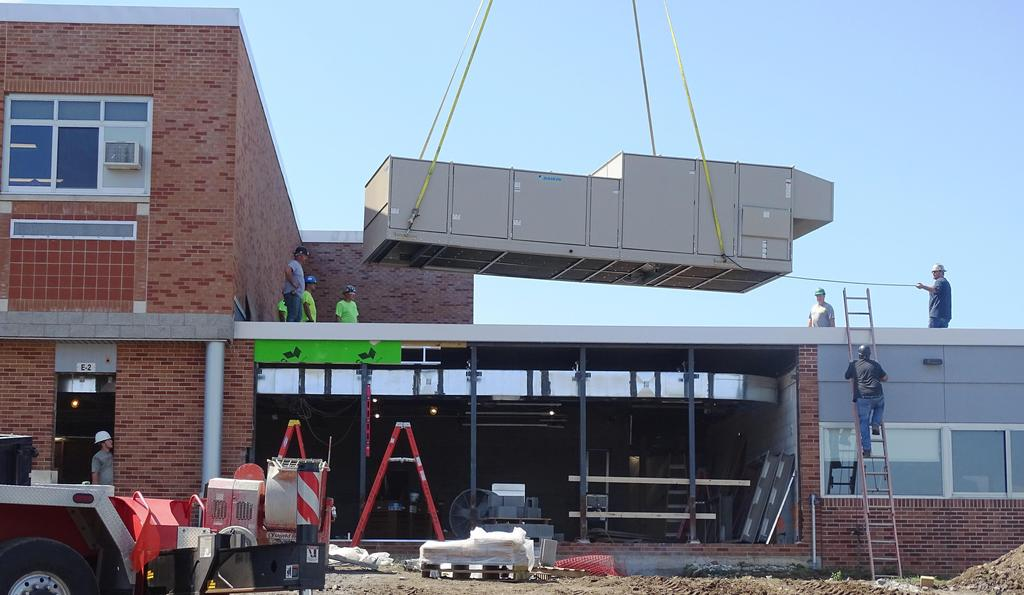 Featured in this snapshot captured during the week of August 9th is a heating and ventilation system rooftop unit being lowered by a mobile crane onto the roof section of what will soon be the new Beekmantown Elementary School cafeteria. That rooftop unit will provide ventilation system services for that entire section of that elementary school.
