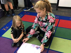 Kindergartner studies book with older student