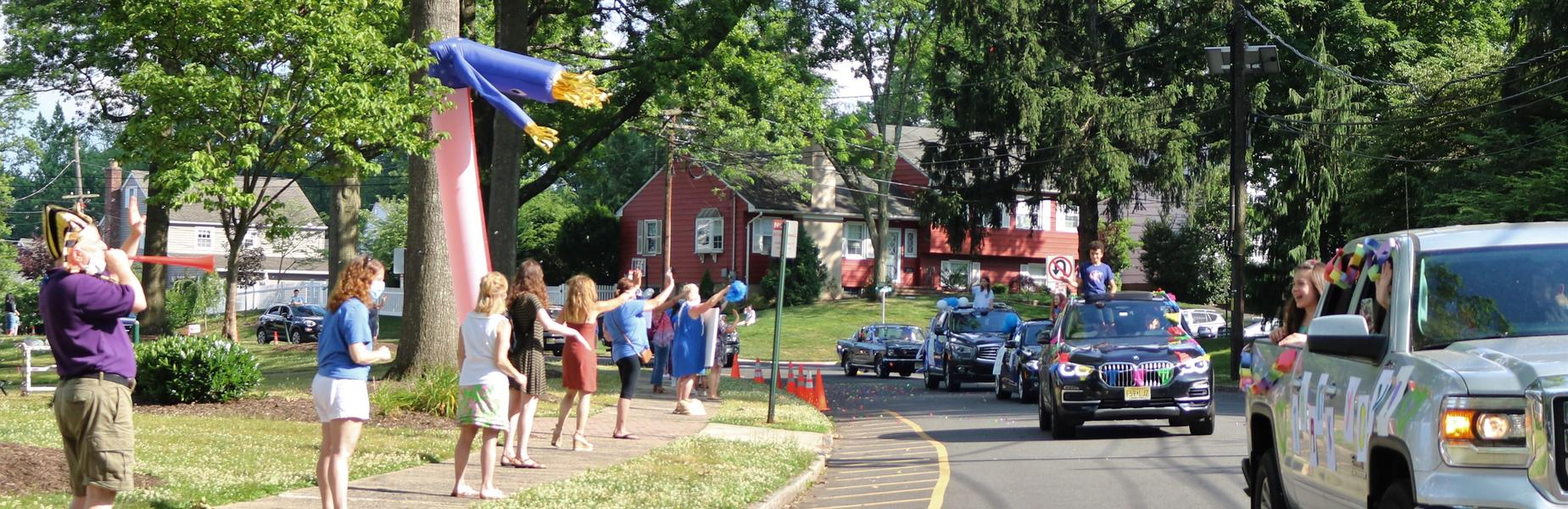 Photo of Washington principal and staff waving to 5th graders during Grade 5 Clap Out Car Parade.