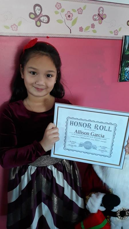 Allison holding honor roll certificate