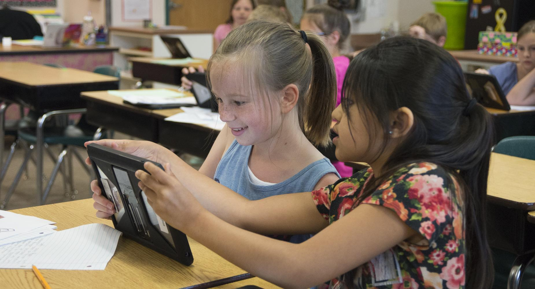 two girls read ipad