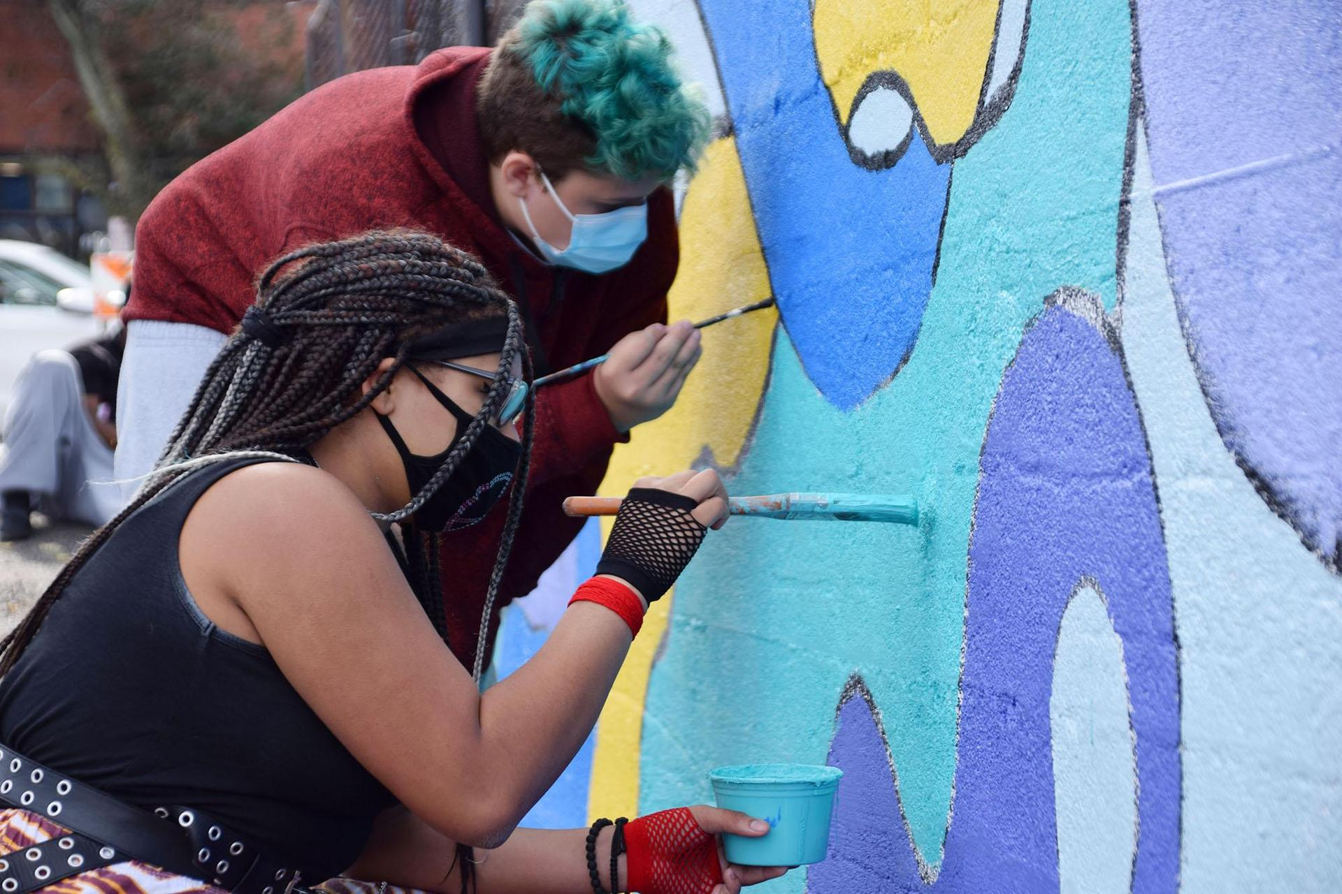 Two women work on the mural together