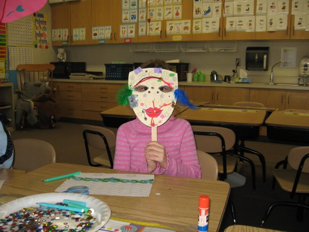 girl poses for camera with mask she made