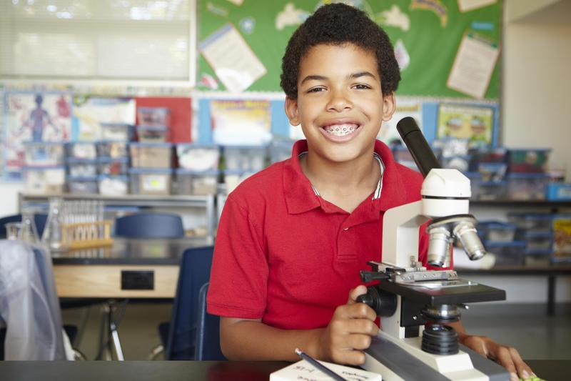 ACES Tech student with microscope
