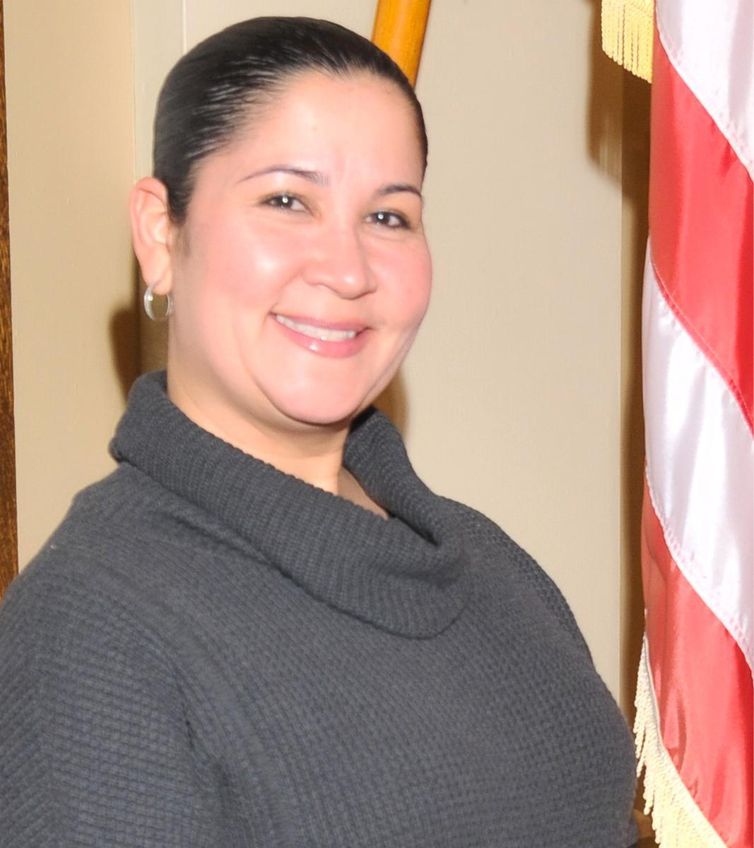 Portrait photo of Jeanette Velez, smiling wide, standing next to an American flag