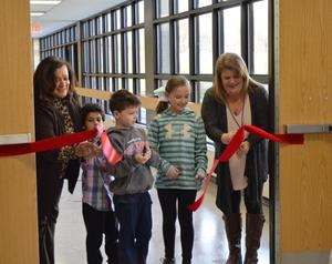 Valley principal Mrs. Toller and 2 boys and a girl along with Special Education teacher Ms. Hill cut the red ribbon to open the Sensory Path.