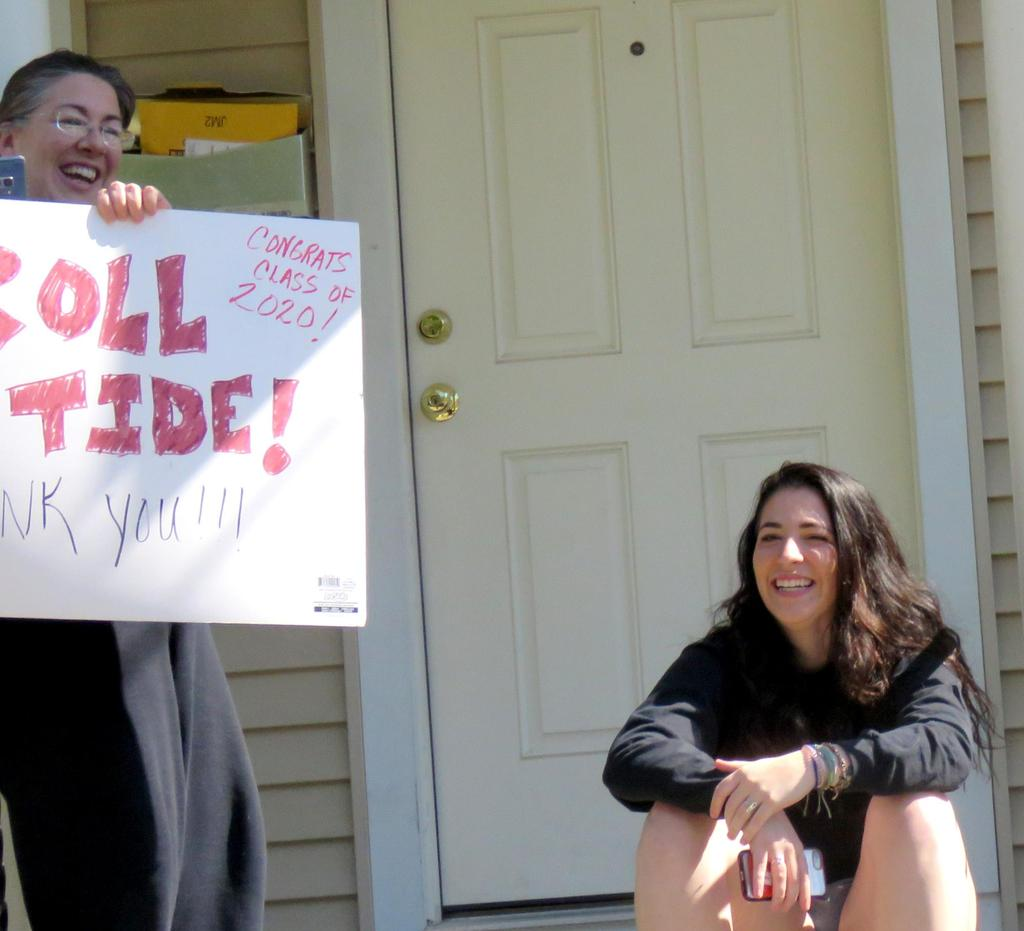 "School Committee member Samantha Lambert holds a ""Roll Tide"" sign on her front porch"