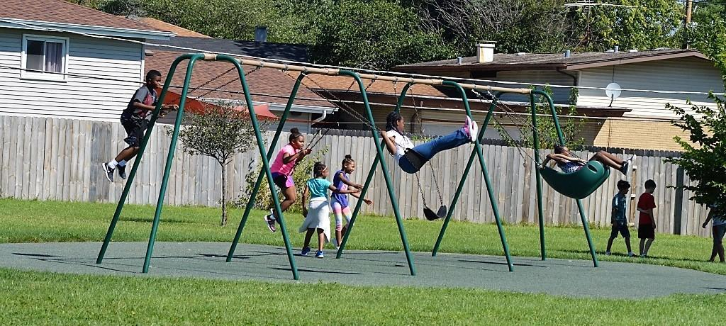 Churchill School students playing on the swings