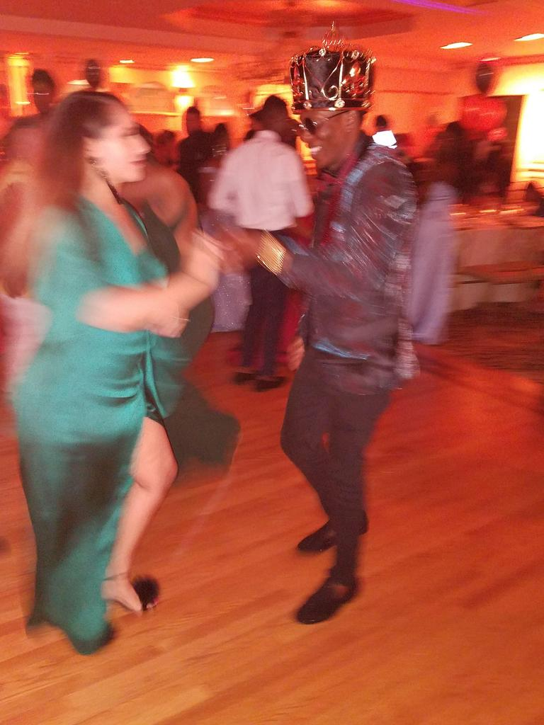 Prom king dancing with another student wearing a dress