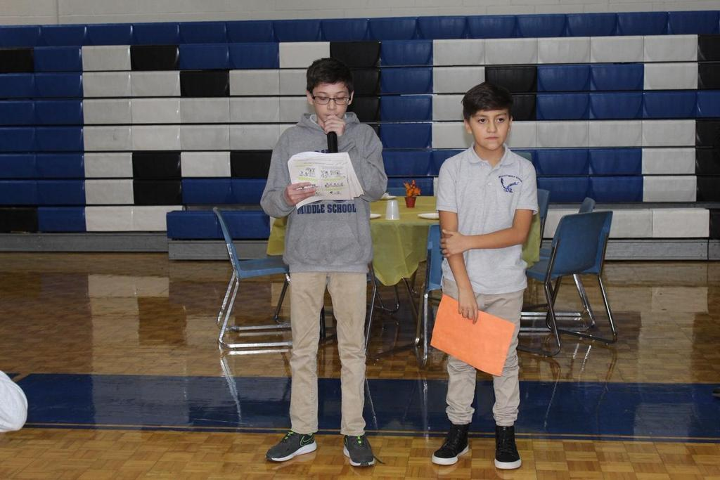 two boys reading a poem they wrote for the Thanksgiving Luncheon