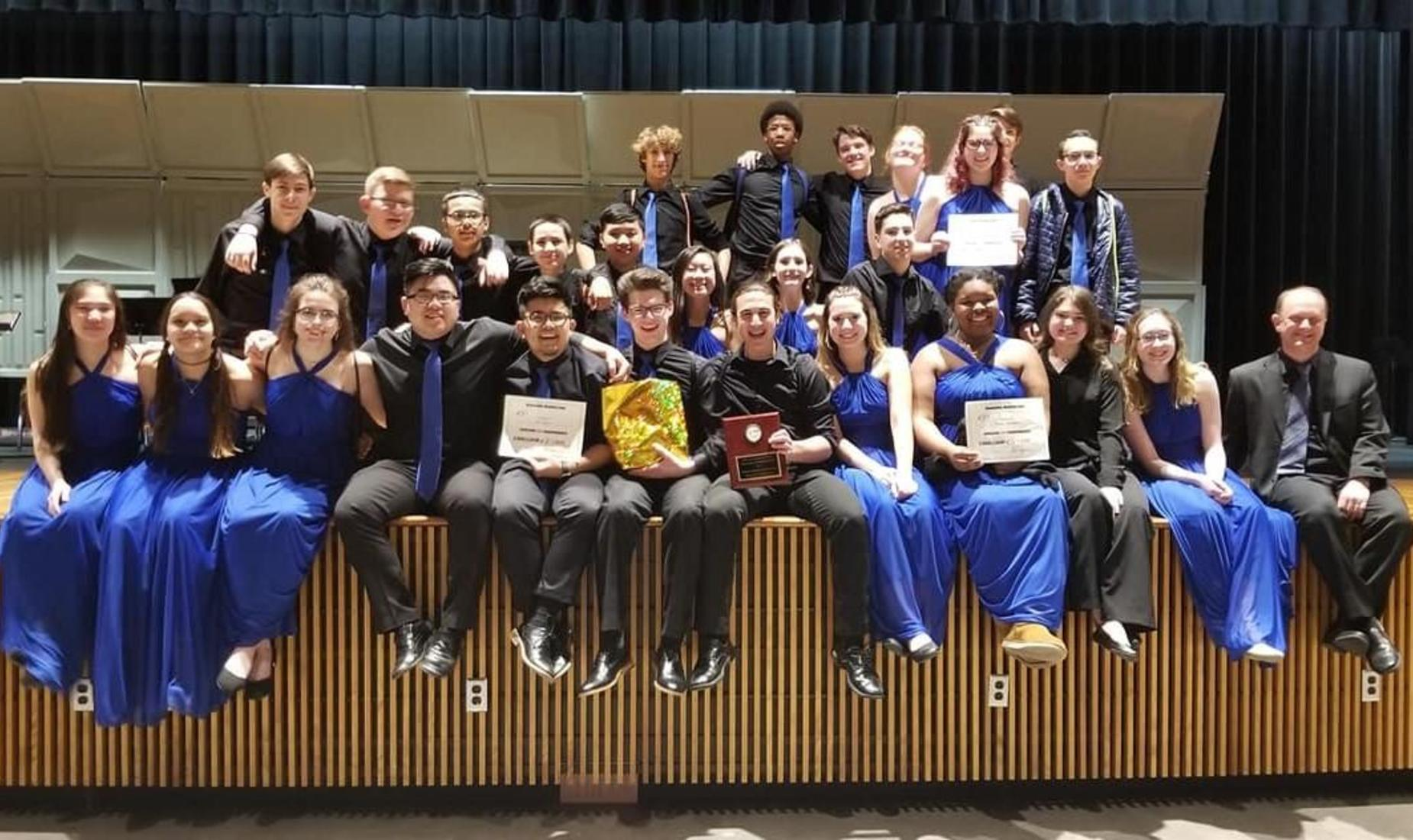 BHS Jazz Ensemble holding their Superior rating plaque. Ladies dressed in royal blue gowns and guys wearing black dress shirts with royal blue ties.