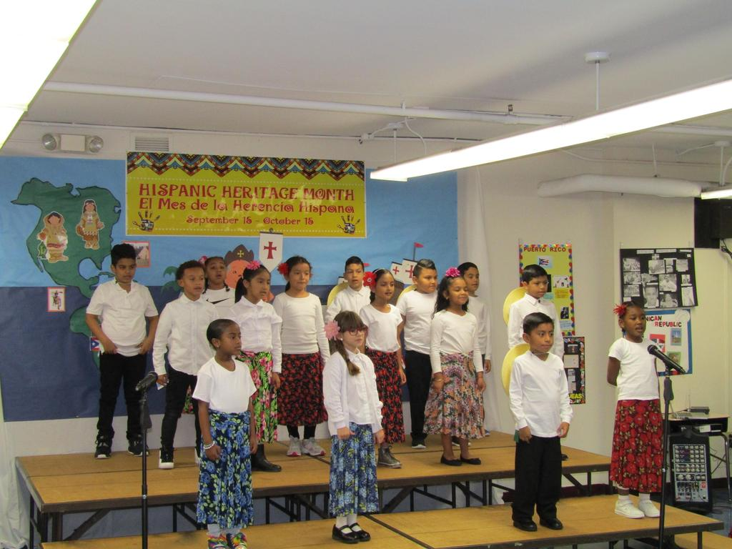 group of girls and boys on stage singing