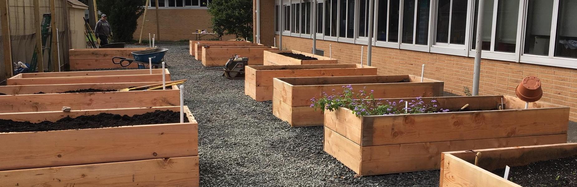 Jefferson School garden committee braves chilly, wet temps to hold garden building party with more than 50 parents & students pitching in to build 12 sturdy garden boxes. Cool weather planting to come.  Pictured here are the 12 newly constructed garden boxes for planting.