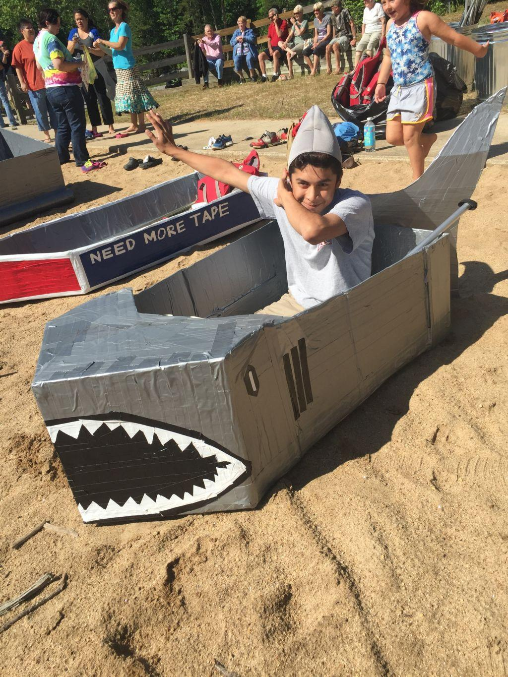 student posing in shark boat before the race