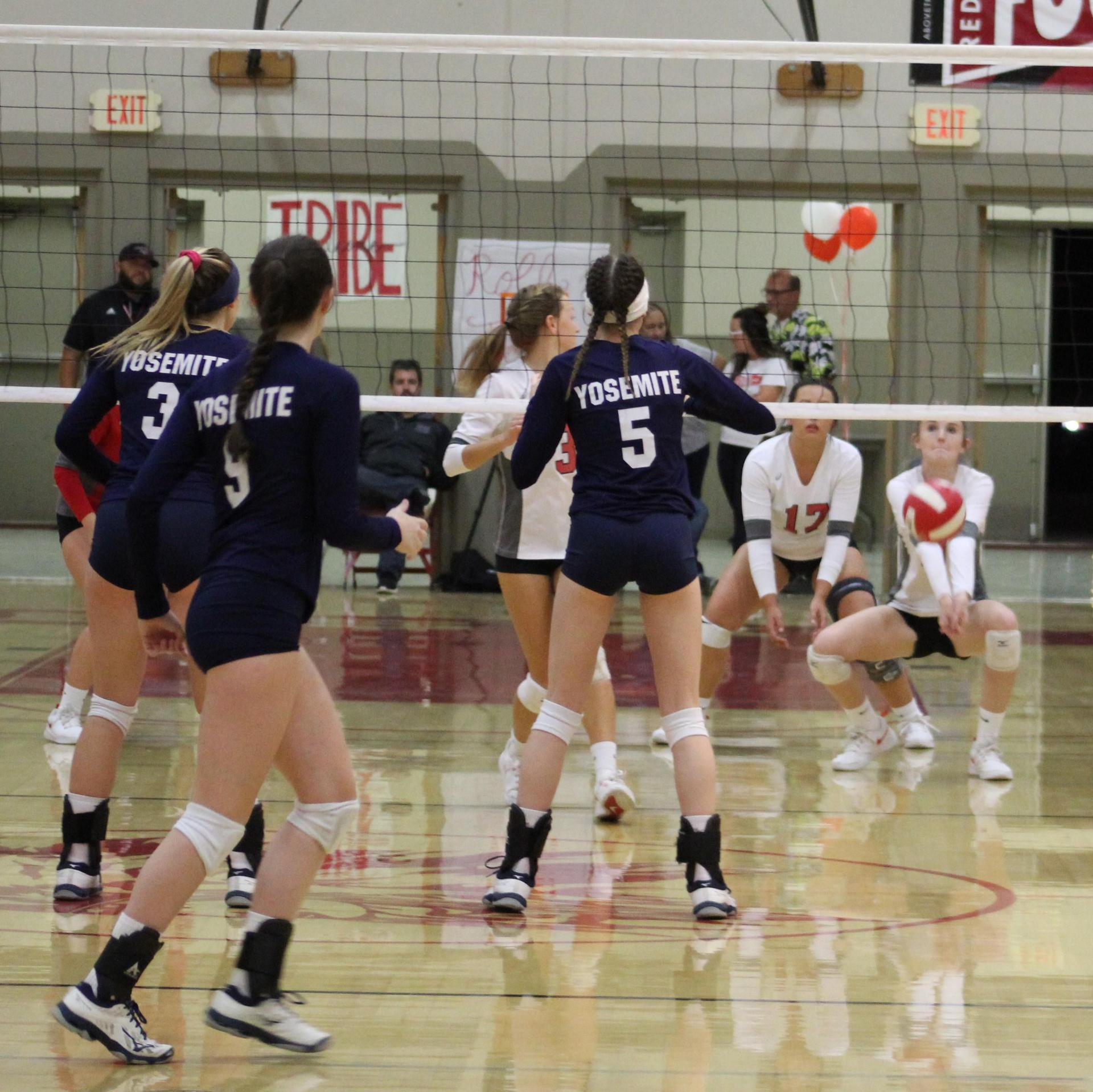 Girls playing varsity volleyball