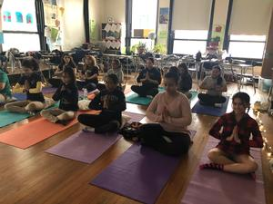 Students sitting on mats to do yoga