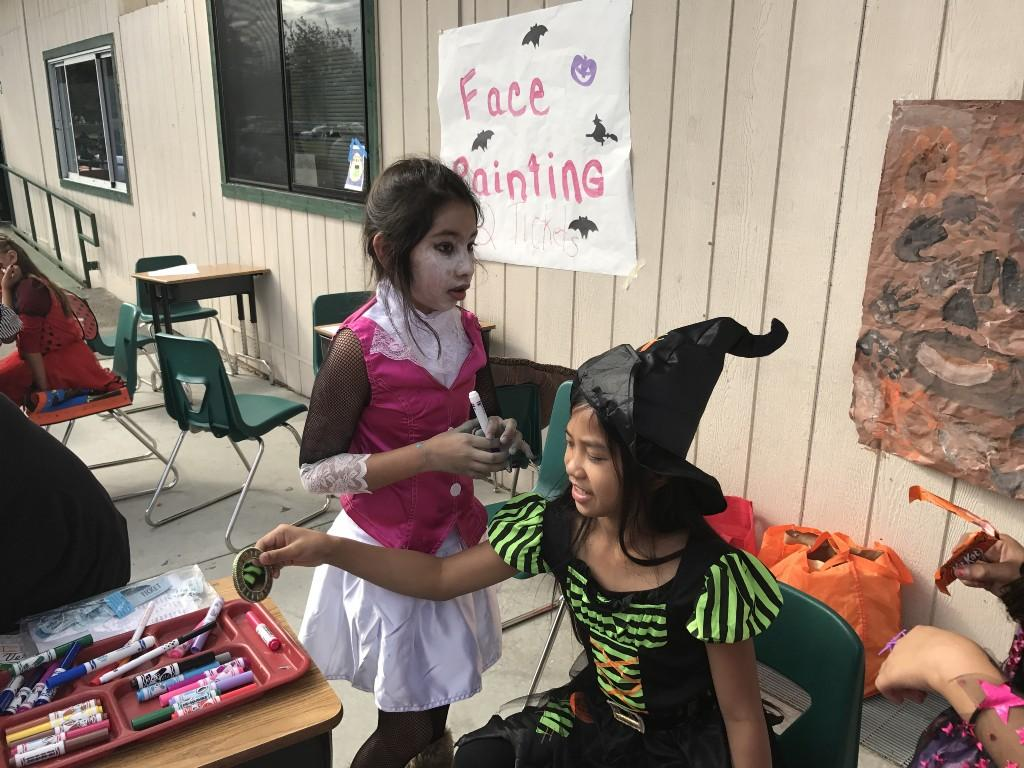 Students helping with face painting booth
