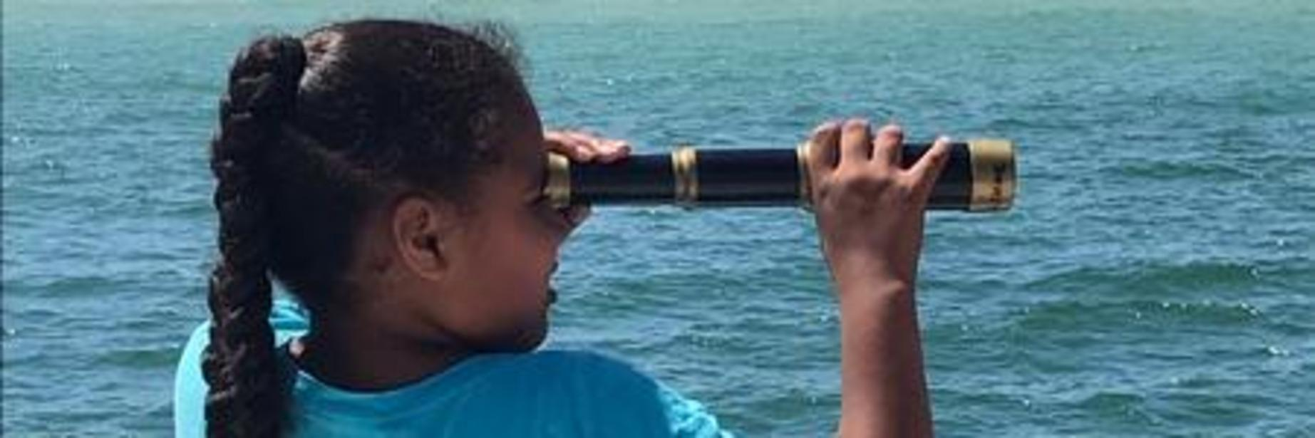 Girl is looking through spyglass on pirate ship