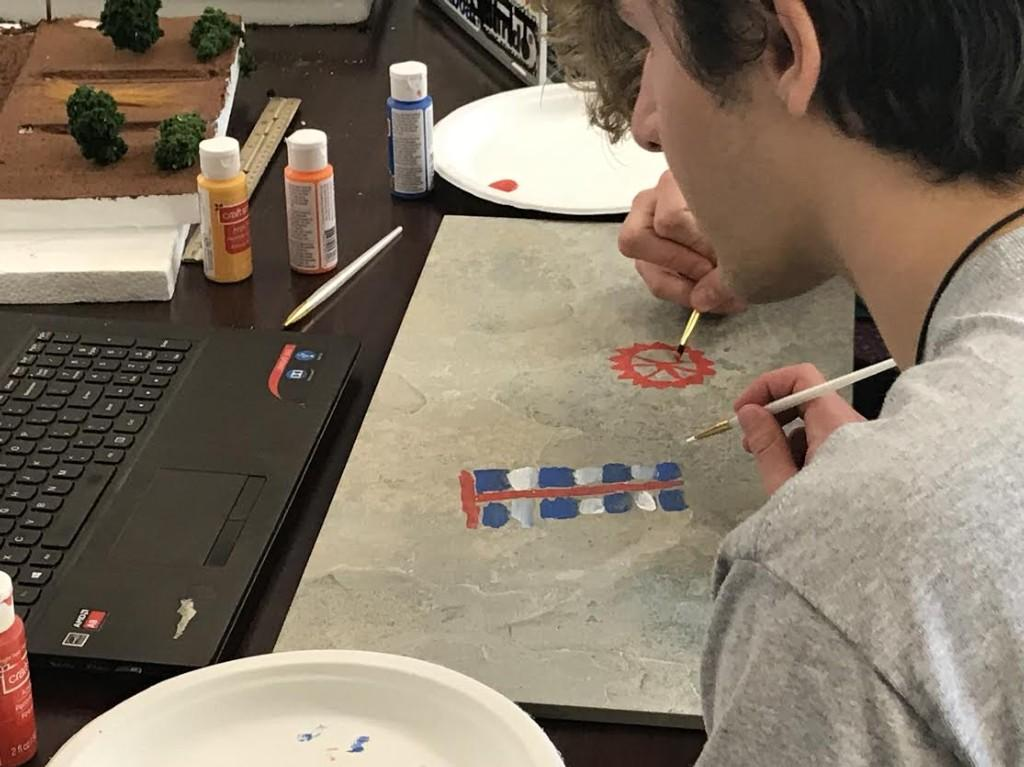 Archaeology students paint ancient cave art on stone slabs