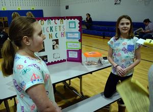 Two girls explain their science fair project.