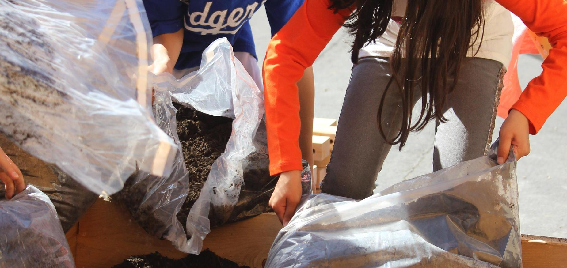 Students pouring dirt into the garden box