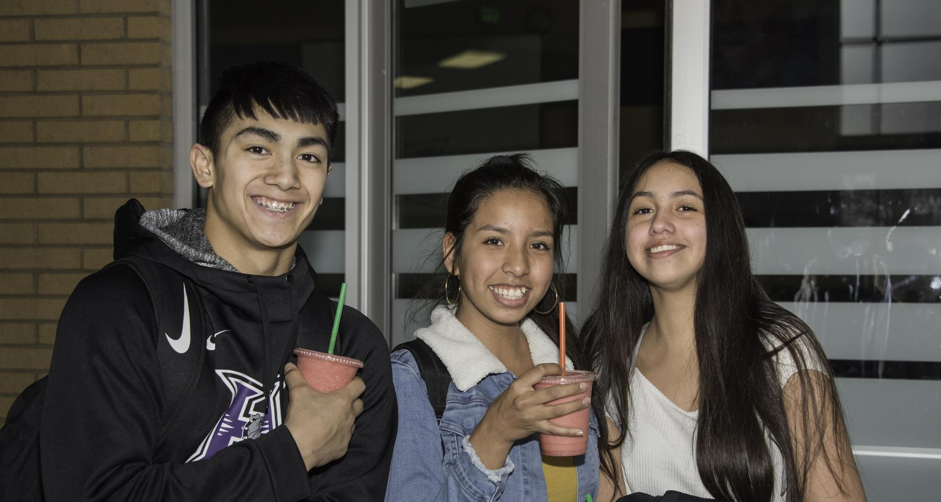 students smiling and holding smoothie drinks