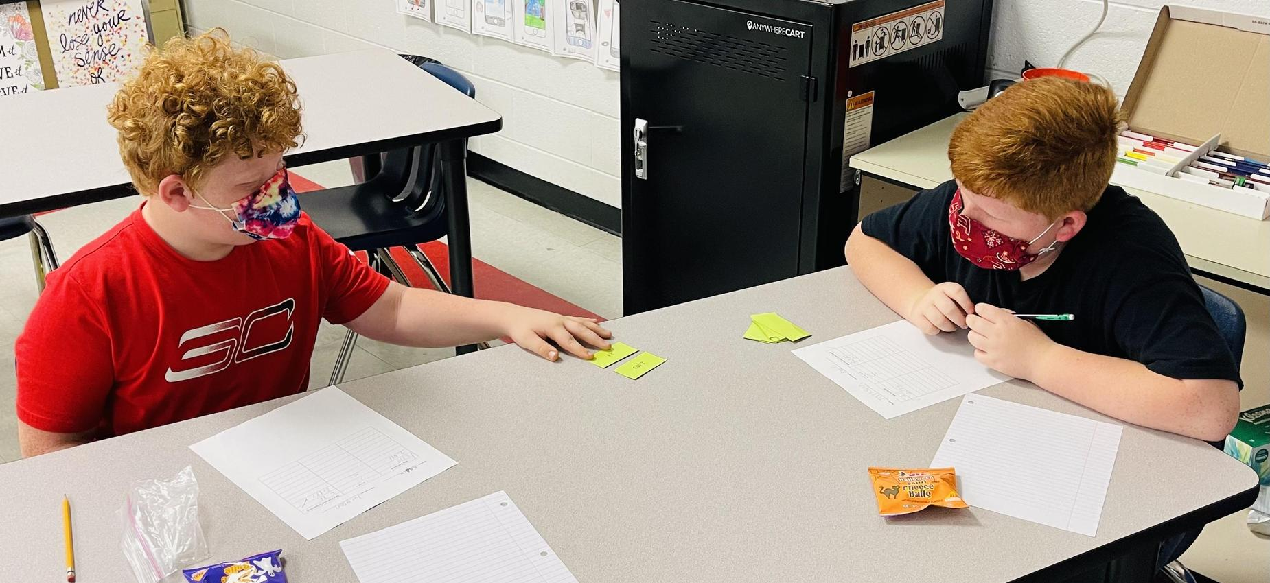 Two students work on math in a classroom.