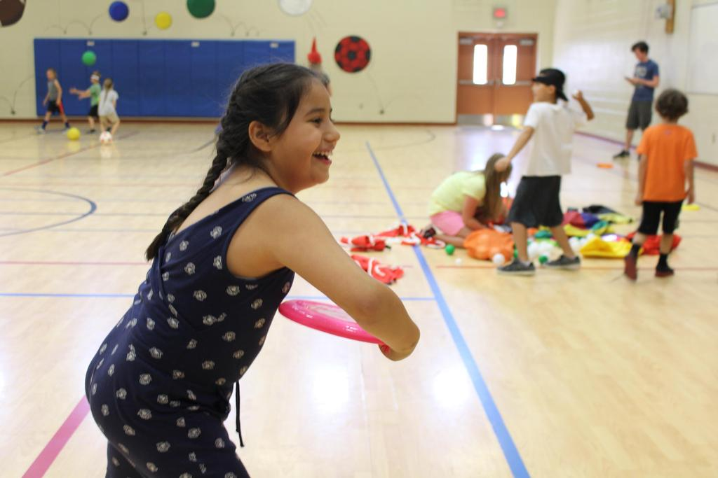 Camper, Sophia Gutierrez, plays Frisbee in the Jacob's Well Elementary School Gymnasium during recreation time at Camp Good Sam.